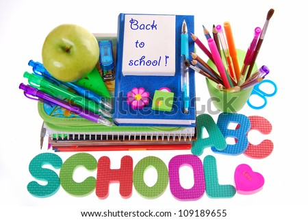 "school equipment with color pencils ,ball pens,books,letters,apple and text ""back to school"" written on white board - stock photo"