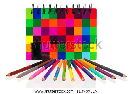 School exercise-book with colour pencils on white background