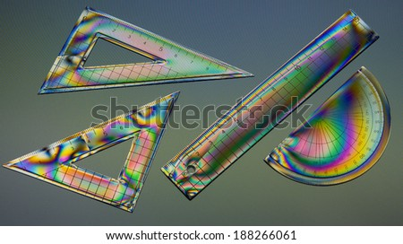 School geometry maths equipment - set squares and ruler, rule. Rainbow colours from interference stress pattern on computer screen. - stock photo