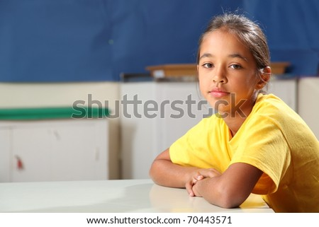 School girl arms folded at her classroom desk