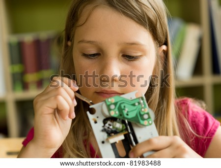 School girl busy with tools and mechanism - stock photo