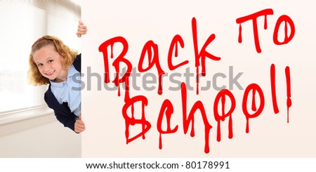 School girl child in uniform looking out from behind graffiti Back To School wall. - stock photo