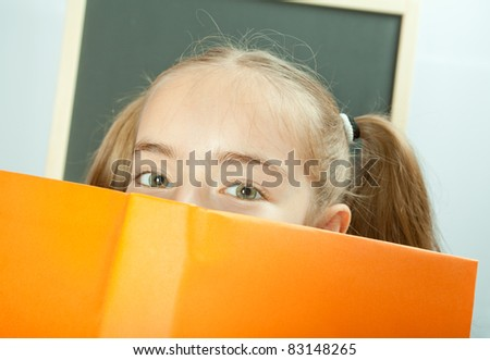 School girl hiding behind yellow book - stock photo