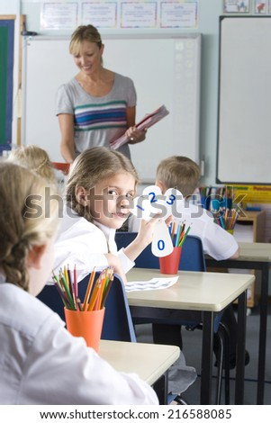 School girl holding number cards at desk in classroom - stock photo
