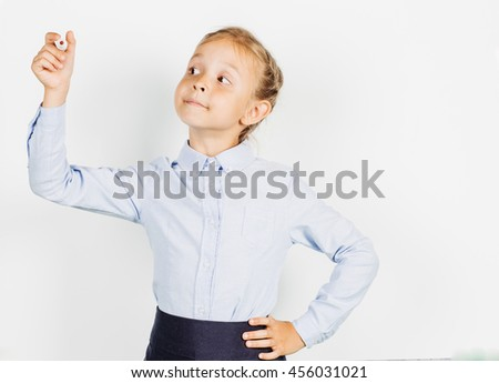 school girl in a school uniform writing something on board with a marker. Learning and school concept. Image on white background. - stock photo