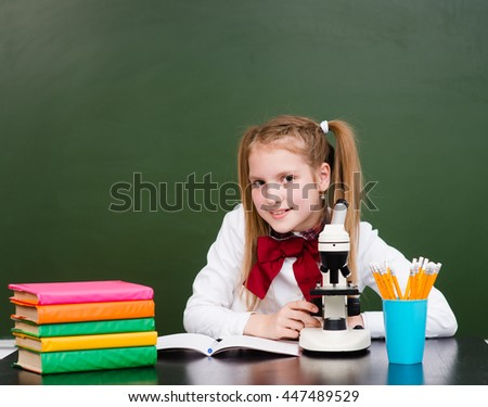 School girl in classroom with microscope