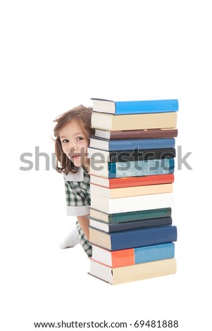 School girl in uniform hiding behind pile of books. Isolated on white.