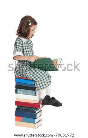 School girl in uniform sitting on stack of books reading. Isolated on white. - stock photo