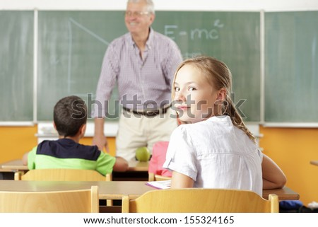 School girl is smiling in the classroom