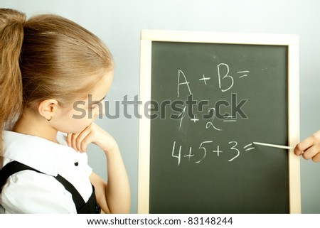 School girl looking at the blackboard with exercises and thinking about answers - stock photo