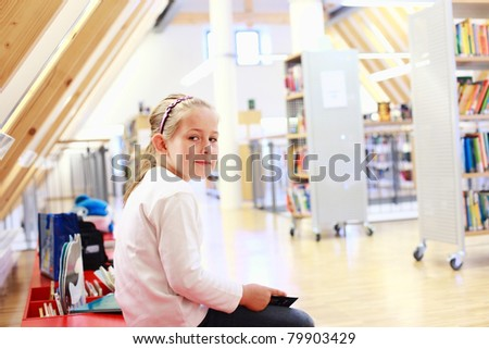 School girl reading a book in library - stock photo