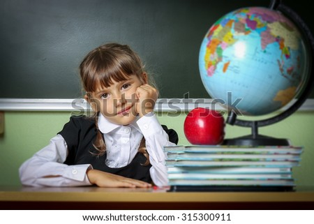 school, girl, schoolgirl 6 years in a black dress and a white shirt with two pigtails on the table Globe and red apple, microscope