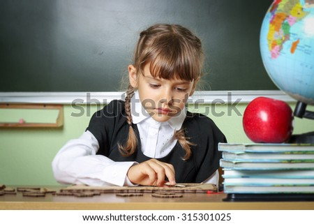school, girl, schoolgirl 6 years in a black dress and a white shirt with two pigtails on the table Globe and red apple, microscope - stock photo
