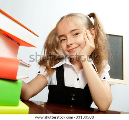 School girl sitting at the table with books.