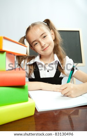 School girl sitting on the table with books. Writing in copybook. - stock photo