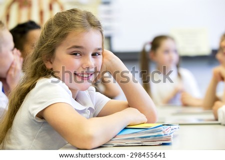 School girl smiles at the camera as she sits at her desk while resting on a big pile of paperwork. - stock photo