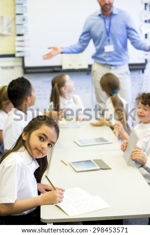 School girl smiles at the camera as she sits at her desk while working.