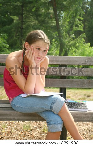 School girl thinking and working on difficult homework assignment in a park on a bench - stock photo