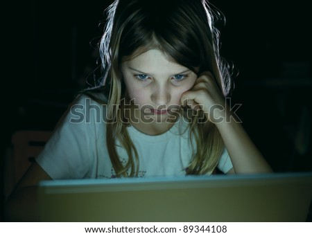 School girl using notebook late in the evening - stock photo