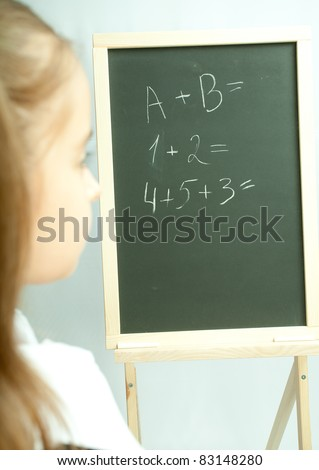 School girl view on the blackboard. Back view. - stock photo