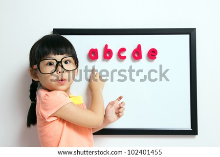 School girl wears a big spectacles posing next to a white board - stock photo