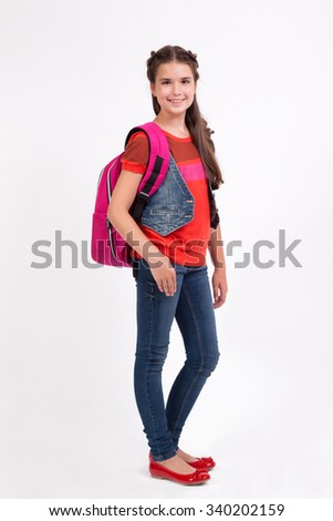 school girl with a backpack standing in jeans on a white background and smiling. - stock photo