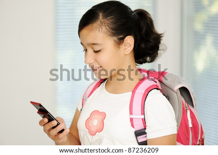 School girl with cell phone, talking and smiling - stock photo