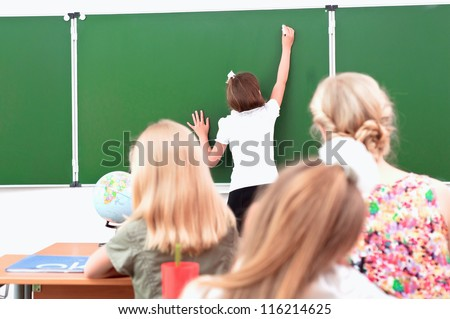 school girl writes on the blackboard in class sitting other students and a teacher and look at the board - stock photo
