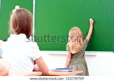 school girl writes on the blackboard in class sitting other students and look at the board