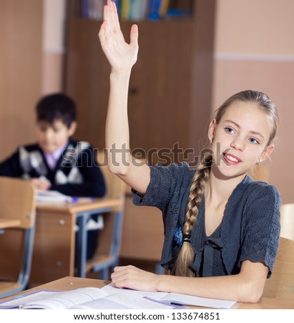 school girls sitting at their desk  and raising hand