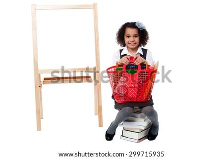 School kid sitting on stack of books near board - stock photo