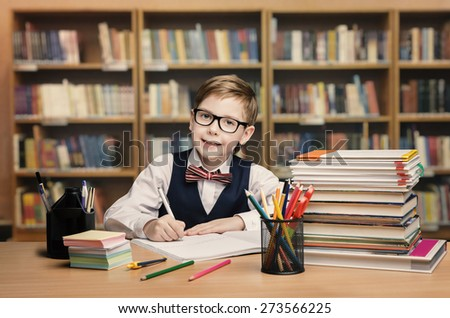 School Kid Studying in Library, Child Writing Paper Copy Book in Classroom with Shelves - stock photo