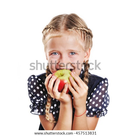 School kid with plaits bites apple. Cute little girl at white background.