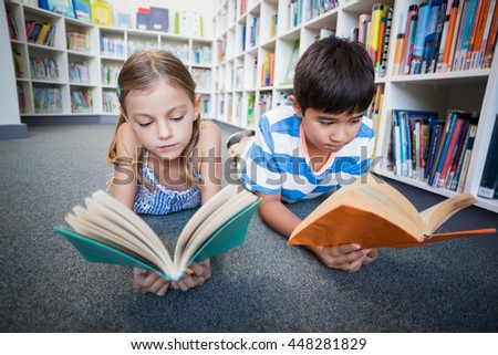 School kids lying on floor and reading a book in library at school - stock photo
