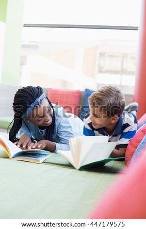 School kids lying on sofa and reading book in library - stock photo