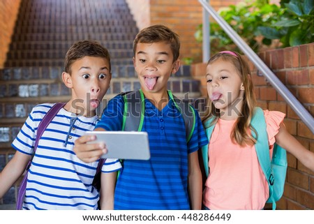 School kids taking selfie from mobile phone at school - stock photo