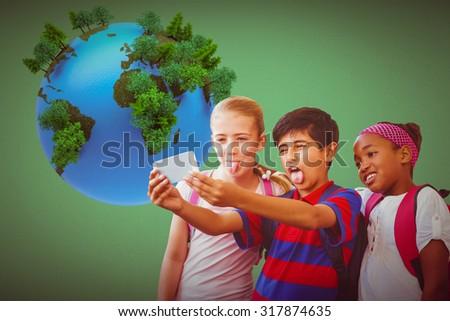 School kids taking selfie in school corridor against green - stock photo
