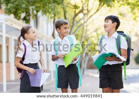 School kids talking to each other while reading books in campus at school - stock photo