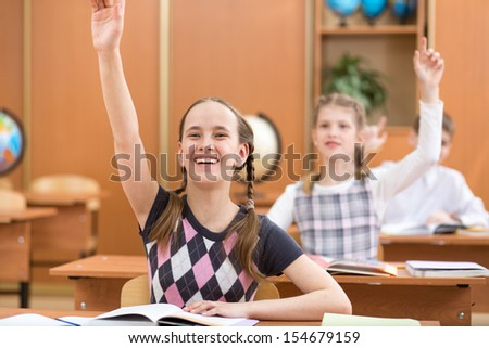 school kids with raised hands at lesson in classroom - stock photo