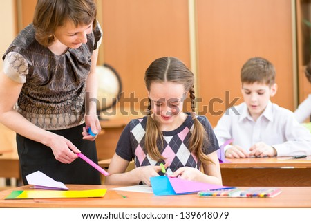 School kids work at labour lesson. Teacher looking at pupil. - stock photo