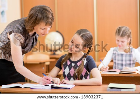 School kids work at lesson in classroom. Teacher controlling learning process. - stock photo