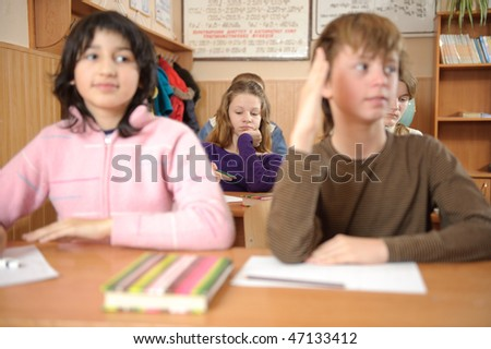 School life routine. Bored girl on second desk is in primary focus. Shallow depth of field. - stock photo