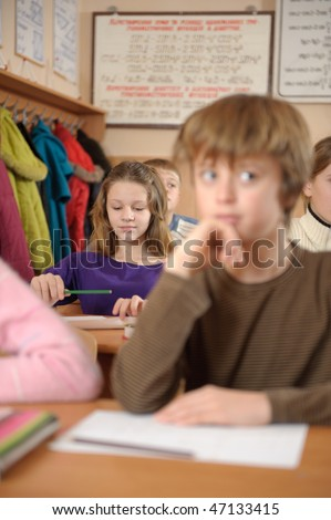 School life routine. Cute girl on second desk is in primary focus. - stock photo