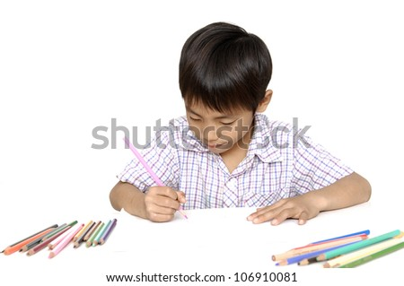 School little boy sitting and writing in books