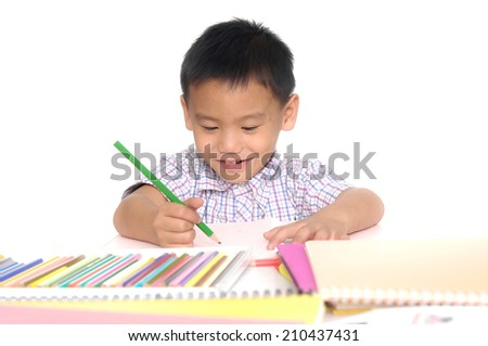 School little boy sitting and writing in books-close up