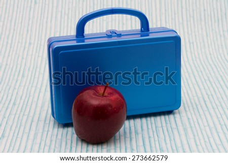 School Lunch, A Blue Lunch Box and a Red Apple over a distressed wood background - stock photo