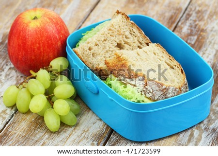 School lunch consisting of rustic bread sandwiches with cheese and lettuce, apple and grapes