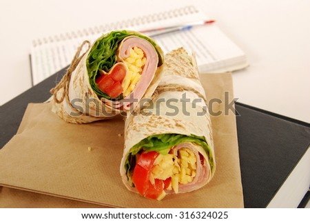 School lunch: ham and cheese wrap sandwich on book