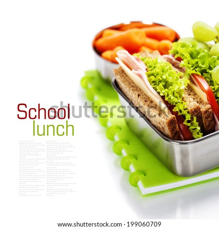 School lunch with a  ham sandwich, apple, grapes and textbooks  - stock photo