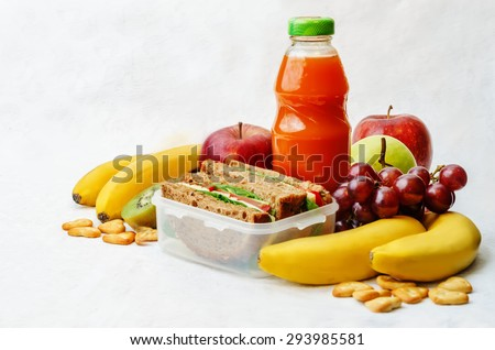 school lunch with a sandwich, fresh fruits, crackers and juice. the toning. selective focus - stock photo